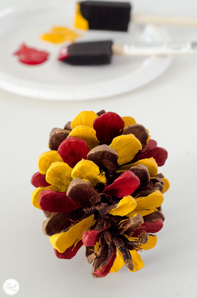 red and yellow painted pinecone for a pinecone turkey craft